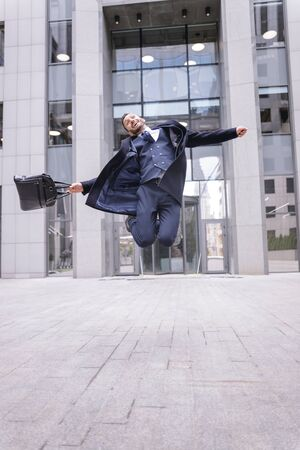 Joyful mood. Kind male person keeping smile on his face while jumping high after successful meeting
