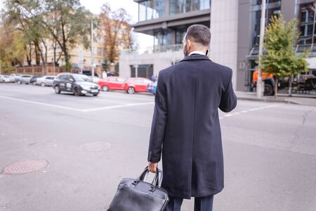Hurry up. Attentive young man wearing stylish coat while arriving to business meeting