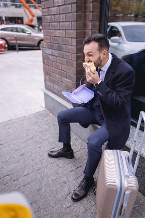 Hurry up. Serious male person biting sandwich while being in a hurry for meeting
