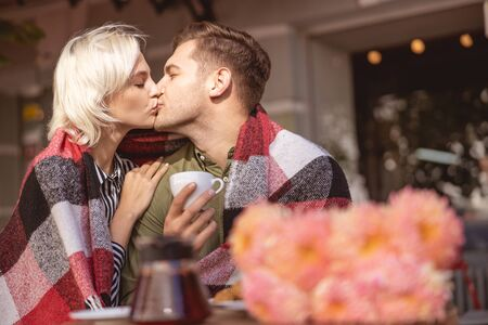 Beautiful couple kissing and sitting under plaid in the coffee shop