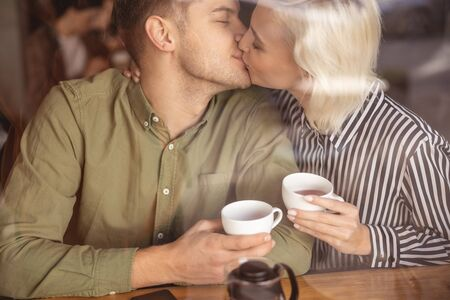 Beautiful young lady with her boyfriend during their tea drinking Reklamní fotografie