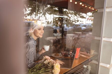 Beautiful young woman sitting at the table behind big cafe window
