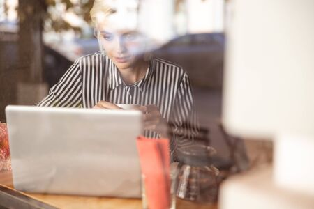 Beautiful young female sitting near cafe window and her laptop