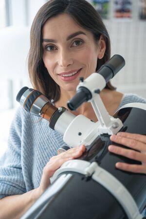 Joyful lady standing with a modern telescope indoors