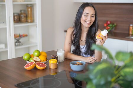Ragazza sorridente con una bottiglia di vitamine seduta al tavolo della cucina Archivio Fotografico