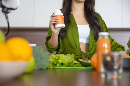 Cropped photo of a female holding a nutritional supplement Reklamní fotografie