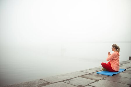 Lady sitting on yoga mat and meditating in lotus position stock photo. Template banner Stock Photo