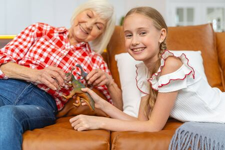 Joyous female with toys reclining on the sofa next to a granddaughter