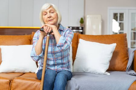 Front view of an elderly woman dozing off on the sofa