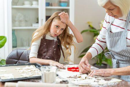 Müde junge Bäckerin, die am Küchentisch sitzt