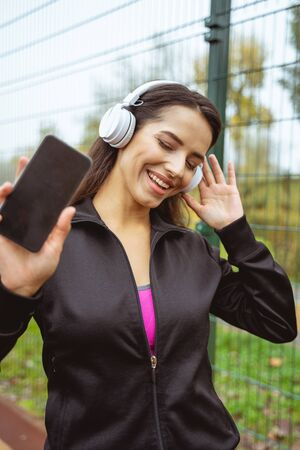 Here I am. Young female person wearing headphones, listening to music