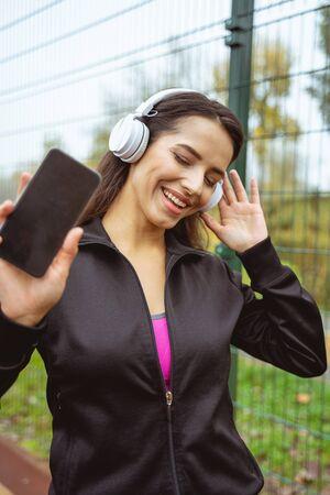 Hier ben ik. Jonge vrouwelijke persoon die een koptelefoon draagt, naar muziek luistert