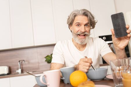 High-spirited attractive modern man sitting at the kitchen table