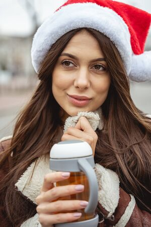 Positive thoughts. Thoughtful girl wearing festive hat while walking in the city center