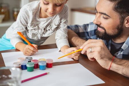 Adorable little girl drawing while spending time with father at home stock photo Stock Photo - 136856008