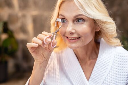 Joyous modern adult lady curling her eyelashes at home