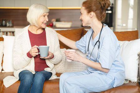 Freundliche Gespräche. Hübsche junge medizinische Mitarbeiterin, die in der Nähe ihres Patienten sitzt und nach Beratung Tee trinken wird