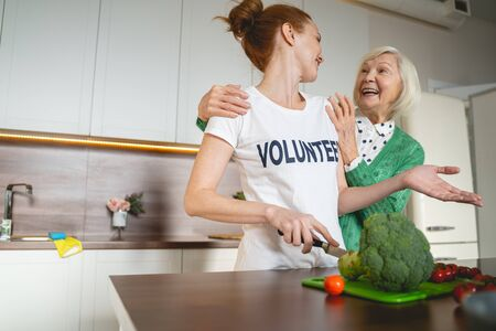 Feeling happiness. Kind volunteer listening to her aged friend while cooking dinner