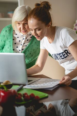 Look here. Kind brunette female looking downwards while teaching pensioner to use computer