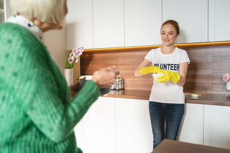 Moment of happiness. Kind volunteer leaning on furniture while listening to mature woman