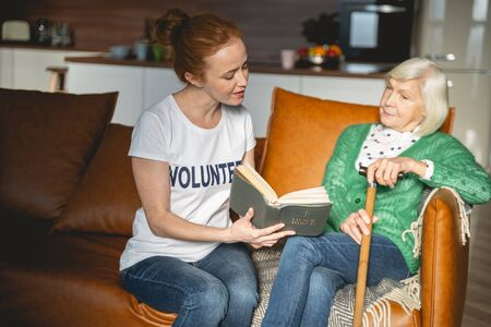 Kind volunteer spending day with pensioner and reading Holy Bible