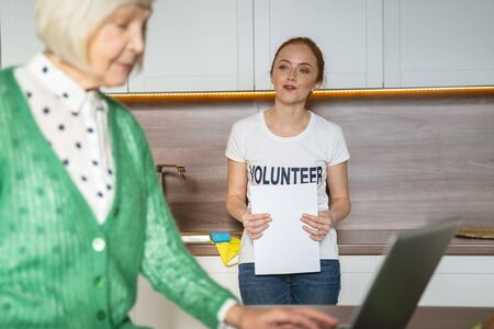 Delighted volunteer leaning on furniture and talking to her aged friend