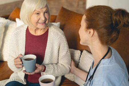 Kind blonde woman keeping smile on her face while drinking tea during conversation