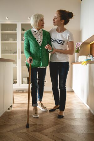 Kind pensioner leaning on walking stick while looking at her helper Banco de Imagens