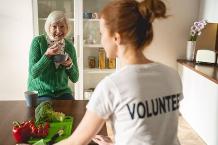 Enjoy your meal. Delighted blonde keeping smile on her face while communicating with young volunteer