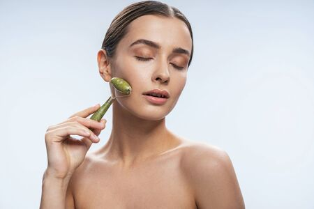 Cute young lady using jade roller. Beauty procedures concept