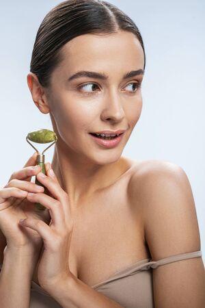 Cute woman using jade roller. Beauty procedures concept
