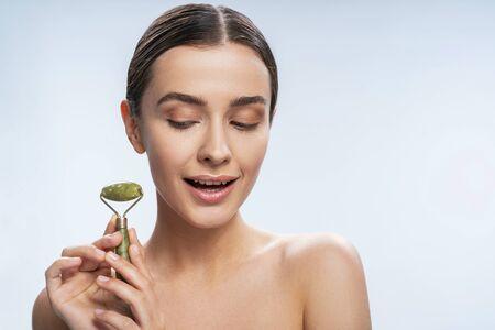 Happy lady using jade roller indoors. Beauty procedures concept