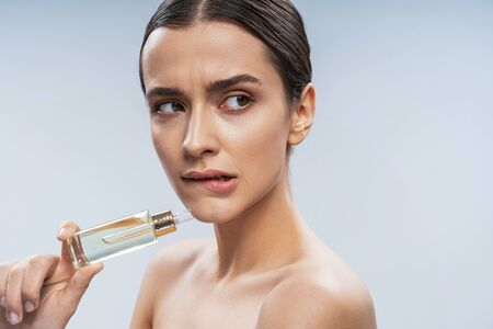 Scared young lady using facial serum. Beauty procedures concept Stock Photo