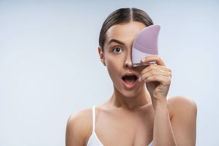 Calm pretty lady takes care of facial skin. Beauty procedures concept
