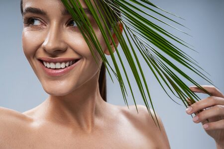 Cute young lady standing near tropical leaf. Female beauty concept