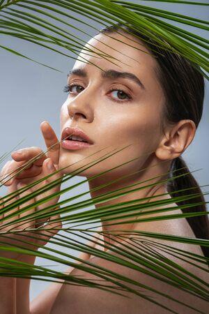 Cute pretty lady standing near tropical leaf. Female beauty concept