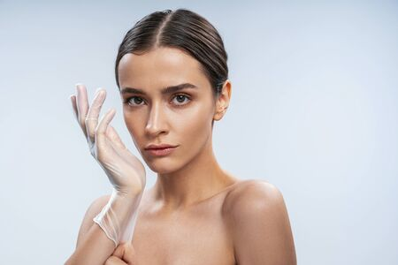 Pretty Caucasian woman in rubber gloves is ready for doing injection. Beauty procedures concept Stock Photo
