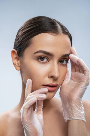 Calm Caucasian woman in rubber gloves is ready for doing injection. Beauty procedures concept