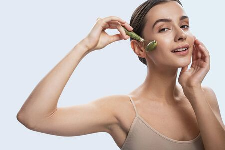 Sexy young lady using jade roller. Beauty procedures concept