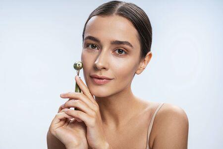 Cute nice woman using jade roller. Beauty procedures concept