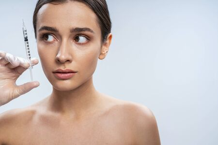 Calm Caucasian woman is getting facial injections in beauty salon. Female beauty and anti-aging concept Stock Photo