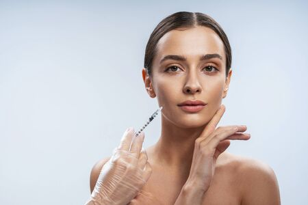 Attractive woman is getting facial injections in beauty salon. Female beauty and anti-aging concept Stock Photo