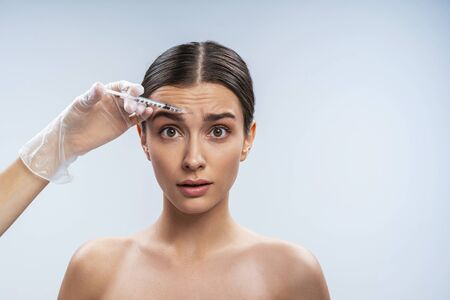 Confused woman is getting facial injections in beauty salon. Female beauty and anti-aging concept