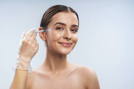 Happy young woman is getting facial injections in beauty salon. Female beauty and anti-aging concept