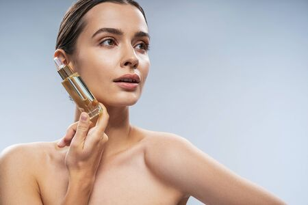 Cute young lady using facial serum. Beauty procedures concept Stock Photo