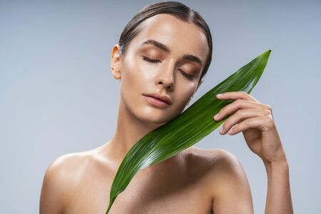 Calm young lady standing near tropical leaf. Female beauty concept