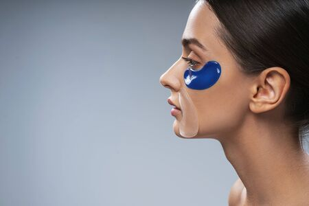 Cute young lady taking care of facial skin and using facial patches. Beauty procedures concept