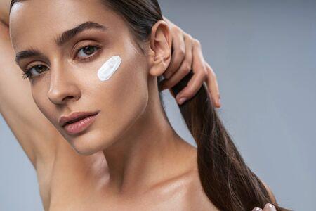 Cute young lady applying facial cream. Beauty procedures concept