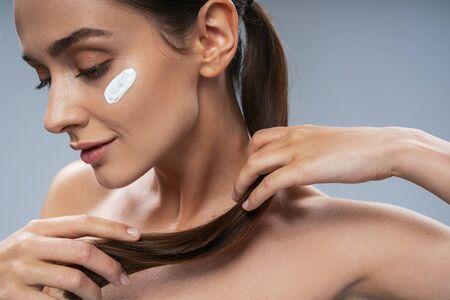 Cute Caucasian lady applying facial cream. Beauty procedures concept