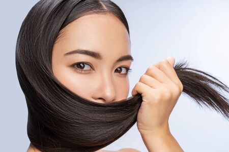 Cute pretty girl keeping her beautiful hair in arm indoors. Personal care concept Imagens
